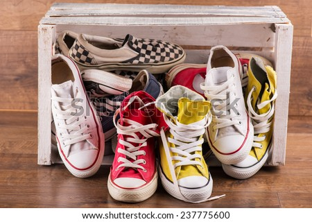 several  pairs of cool youth red blue white yellow  gym shoes falling out white  box   on brown wooden floor