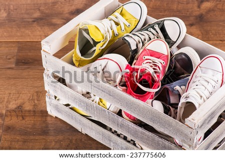 several  pairs of cool youth red blue white yellow  gym shoes in box   on brown wooden floor