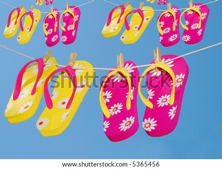 Several pairs of flipflops hanging on clothes lines
