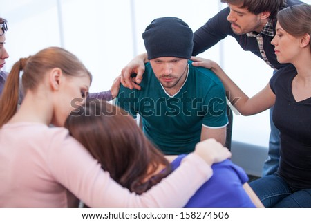 Several people comforting young man on background. Young woman comforting another woman on foreground