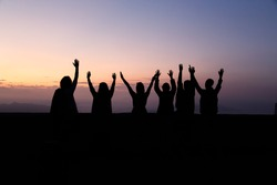 Several people raise their hands up to greet the dawn in the mou