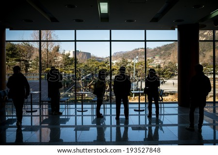 Several people stand in front of french windows