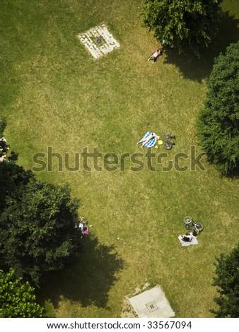 several people sunbathing on lawn on park, birds view