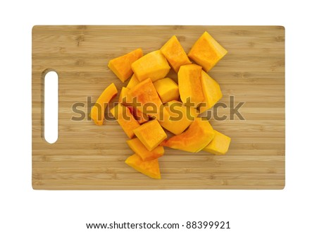 Several pieces of cut butternut squash on a wood cutting board.