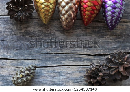 Several pine cones are located on a wooden pallet. Large and small pine cones along with Christmas tree decorations. Top view. Place for text. #1254387148