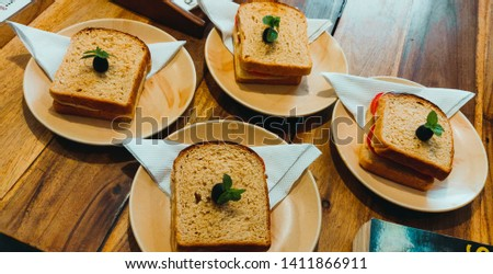 Several plates of brown bread sandwiches on plate which is on polished wooden table #1411866911