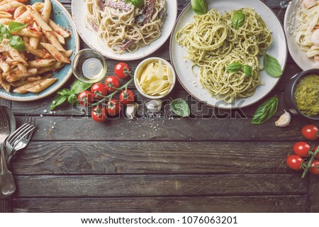 Several plates of pasta with different kinds of sauce over wooden background, top view. Concepts of Italian food.