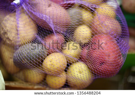 Several potato varieties displayed in a mesh bag at the grocery store for sale as a variety pack.  Red potatoes, russet, fingerling, white, yellow, blue/purple.