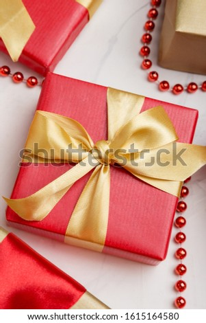 Several present boxes at white background. Red presents with golden ribbons for holidays.