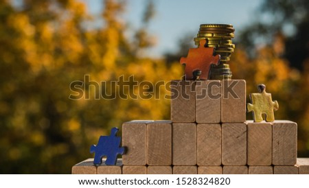Several puzzles climb to the top of the pyramid made of wooden blocks. The concept of achieving business goals and reaching new levels of promotion.
