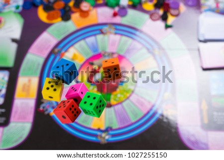 Several rolling color dice fall on a table with board game. Gaming moments in dynamics. copy space #1027255150
