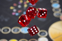 Several rolling red dice fall on a table with boardgame. Gameplay moments.