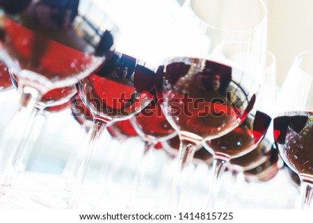 Several rows glasses with red wine on counter prepared for guests. Catering and guest service at the event. Luxury nightlife, holidays and festival. Soft focus beautiful bokeh. #1414815725