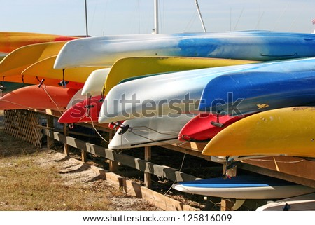 Several rows of pretty, brightly colored canoes