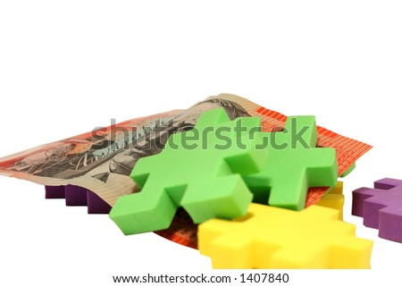 Several scattered foam jigsaw pieces and Australian $20 note isolated over white