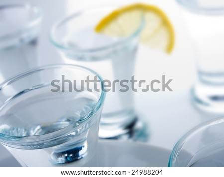 Several short glasses and lemon on the glass table