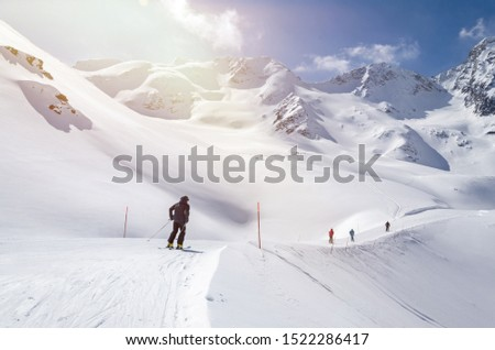 Several skiers skiing down the slope in beautiful snowy mountain landscape #1522286417