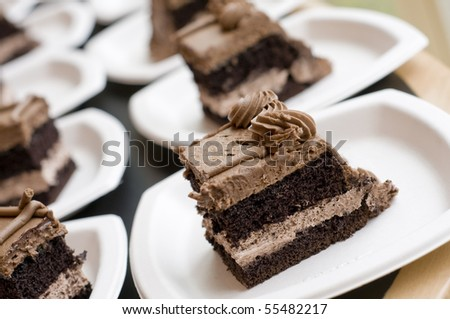 several slices of chocolate cake on white paper plates
