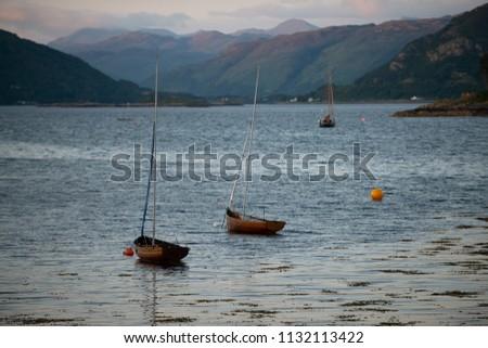Several small boats anchored on the lake at Plockton town, Highlands, Scotland
