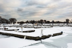 Several snow covered docks sitting in an empty marina with frozen ice sheets on cold winter day with overcast sky in urban Chicago