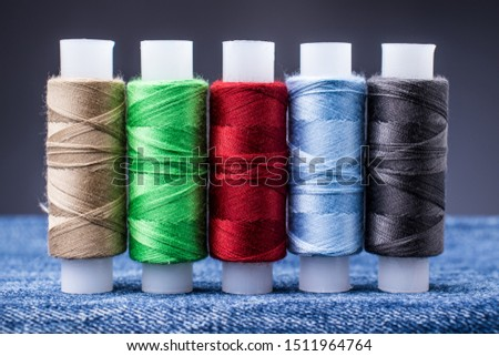 Several spools of colored thread for sewing on denim. Concept needlework and tailoring. #1511964764