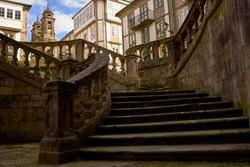 Several stone stairs with houses and a church in the background