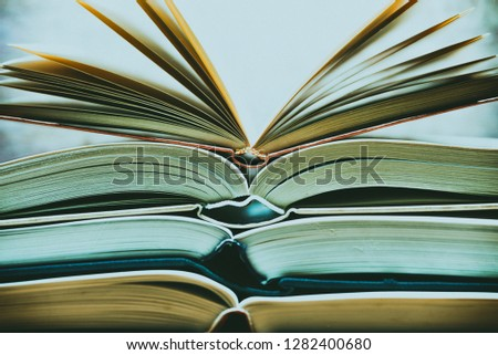 Several textbooks with white sheets opened in the middle #1282400680
