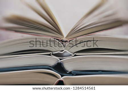 Several textbooks with white sheets opened in the middle #1284514561
