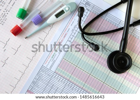 Several type ot tubes for blood tests,  a digital thermometer, and a stethoscope on top of a desk with electrocardiogram tracing and a vital signs record sheet as background. Clinical investigation