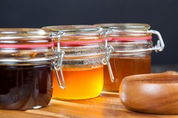 several varieties of honey from different varieties of flower plants, bottled in different jars several different types of honey that differ in color, taste and other characteristics, natural honey