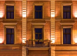 Several windows in a row and balcony on night illuminated facade of Angleterre Hotel front view, St. Petersburg, Russia