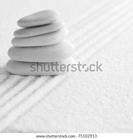 several zen stones on the sand background