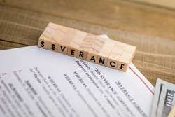 Severance Pay concept with agreement document on wooden board and SEVERANCE spelled out in wood blocks selective focus