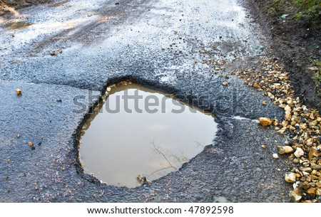 Severe winter damage to a tarmac road producing a large, deep ,waterfilled pothole