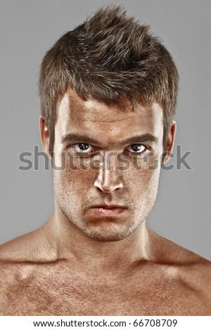 Severe young man lours, on gray background.