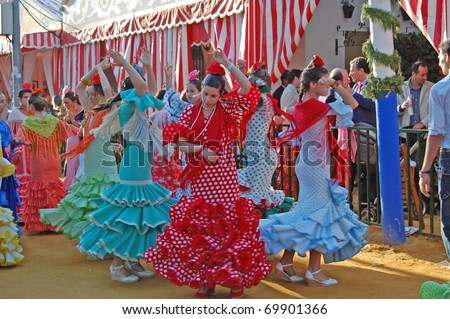SEVILLE - APRIL 28: Young women in traditional flamenco dresses dance during the Feria de Abril on April 28, 2009 in Seville, Spain.