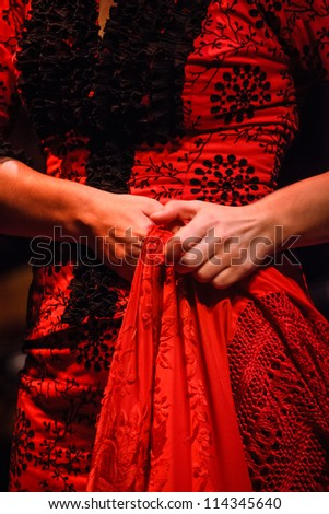 SEVILLE, SPAIN - MAY 1: Detail of a traditional Flamenco dancer red dress costume embroidery and shawl on May 1, 2010 in Seville, Spain. It is very popular in Tucson Arizona's Flamenco Festival