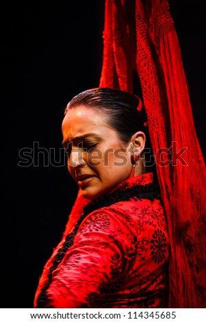 SEVILLE, SPAIN - MAY 1: traditional Andalusian Flamenco dancer in red twists her head in classical pose on May 1, 2010 in Seville, Spain.It is very popular in Tucson Arizona's Flamenco Festival