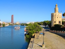 Seville, Spain, October 2016. View of the Guadalquivir quay with the Golden Tower (Torre del Oro), built in the 12th century in the style of Moorish architecture.