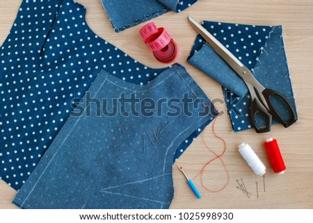 Sew clothes with needles and threads. View from above. Fabric, spools of thread, needles, tailoring scissors, tape measure are needed for sewing clothes. The process of sewing clothes.