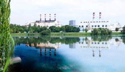 Sewage pipe from a metal pipeline, discharging directly into a natural pond with green grass on the shore against the backdrop of the exhaust pipes of an industrial enterprise.