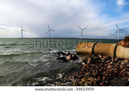 sewage waste pipe and offshore wind mills or turbines. coast with pollution and envirnmental friendly green energy production