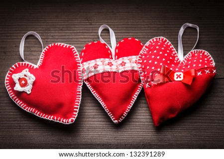 Sewed handmade red hearts on wooden background