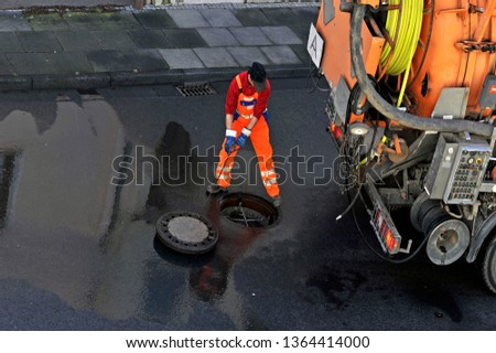 Photo of Sewer cleaning. Sewage worker on cleans pipe