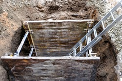 Sewer construction work in the city center with ladder and supporting walls - Top view shaft