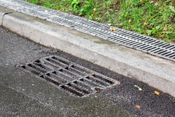 sewer manhole grille on a wet asphalt road after rain near the curb in the background behind the curb a drain channel covered with a grid.
