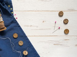 Sewing a button to a blue fabric on a white wooden background