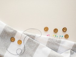 Sewing a button to a stripe fabric on a off-white background