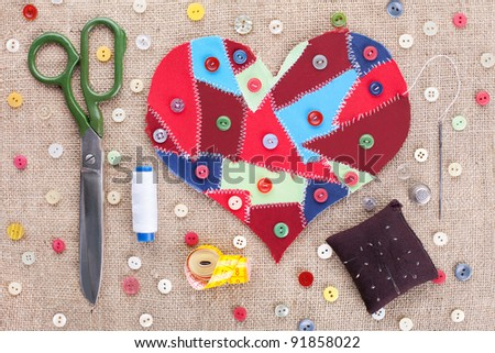 Sewing accessories and fabric scraps heart on fabric texture background . Valentine's Day
