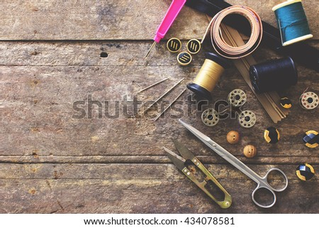 Sewing accessories.  scissors, needle, thimble on wooden table background, over light [vintage tone] #434078581